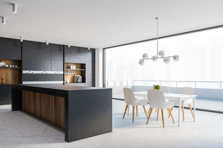 Corner of stylish kitchen with black and wooden walls, tiled floor, comfortable countertops, bar with stools, white dining table with chairs and balcony with blurry cityscape. 3d rendering Reklamní fotografie