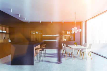Blurry young woman walking in spacious kitchen with black and wooden walls, bar counter with stools and white dining table and balcony with cityscape. Toned image