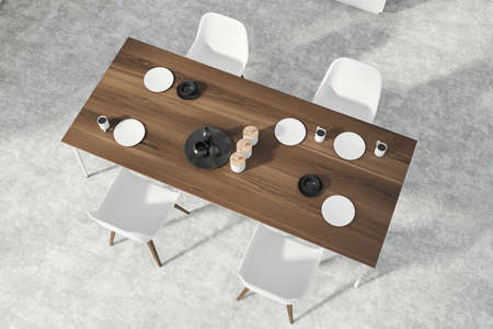 Top view of modern dining room with white walls, concrete floor, long wooden table with dishes and white chairs. 3d rendering