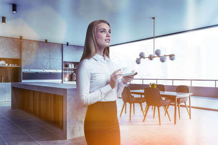 Blonde woman with coffee standing in spacious kitchen with white brick walls, concrete floor, white countertops and dining table with chairs. Blurry cityscape. Toned image Reklamní fotografie