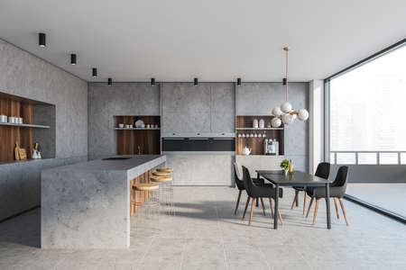 Interior of modern kitchen with stone and wooden walls, tiled floor, comfortable countertops, bar with stools, gray dining table with chairs and balcony with blurry cityscape. 3d rendering