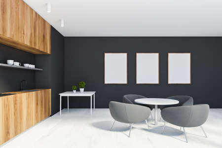 Side view of stylish kitchen with black walls, wooden floor, dark wooden countertops, round dining table with gray armchairs and coffee table. Three vertical mock up posters. 3d rendering