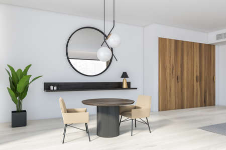 Corner of modern dining room with white walls, wooden floor, round dark wooden table with beige armchairs and round mirror. 3d rendering