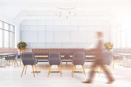 Blurry young man walking in modern kitchen with white brick walls, concrete floor, white countertops and dining table with chairs. Toned image