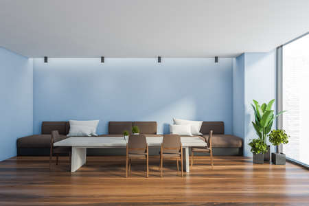 Interior of stylish dining room with blue walls, wooden floor, long table with brown chairs and long comfortable sofa with white cushions. Window with blurry cityscape. 3d rendering