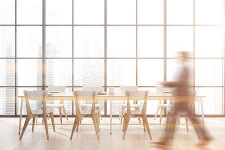 Blurry young man in suit walking in panoramic dining room with wooden floor and long table with white chairs. Window with modern cityscape. Toned image