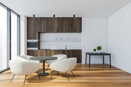 Interior of modern kitchen with white walls, wooden floor, dark wooden countertops, round dining table with white armchairs, coffee table and window with blurry cityscape. 3d rendering