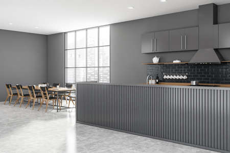 Corner of modern kitchen with gray walls, concrete floor, gray and wooden island and long dining table with gray chairs standing near window with blurry cityscape. 3d rendering Reklamní fotografie