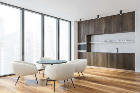 Corner of modern kitchen with white walls, wooden floor, dark wooden countertops, round dining table with white armchairs and window with blurry cityscape. 3d rendering Reklamní fotografie