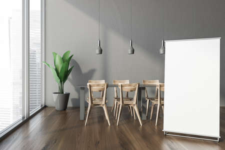 Interior of modern office cafe with gray walls, wooden floor, long dining table with wooden chairs and vertical mock up banner standing near window with blurry cityscape. 3d rendering