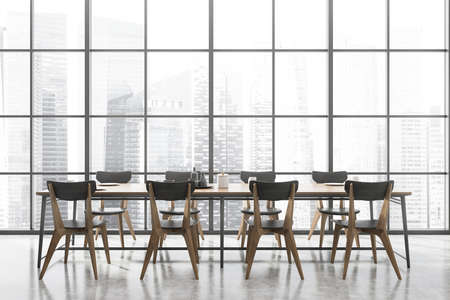 Interior of spacious panoramic dining room with concrete floor, long wooden table with gray chairs and big window with blurry cityscape. 3d rendering