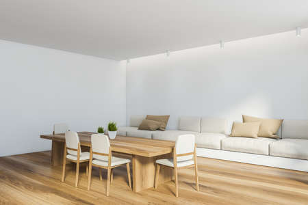 Corner of modern dining room with white walls, wooden floor, long table with white chairs and long comfortable sofa with beige cushions. 3d rendering Reklamní fotografie