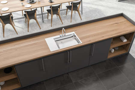 Top view of modern kitchen with concrete and tiled floor, gray and wooden island with built in sink and dining table with gray chairs. 3d rendering