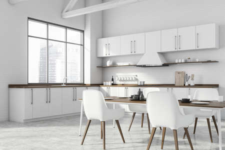 Corner of modern kitchen with white brick walls, concrete floor, white countertops and dining table with white chairs. Window with blurry cityscape. 3d rendering