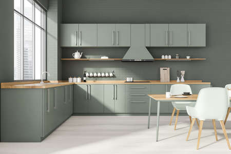 Interior of stylish kitchen with gray brick walls, wooden floor, gray countertops and dining table with white chairs. Window with blurry cityscape. 3d rendering Reklamní fotografie
