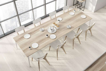 Top view of stylish panoramic dining room with wooden floor, long wooden table with white chairs and big window with blurry cityscape. 3d rendering Reklamní fotografie