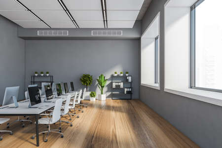 Side view of stylish open space office with gray walls, wooden floor, long white computer table with chairs and windows with blurry cityscape. 3d rendering