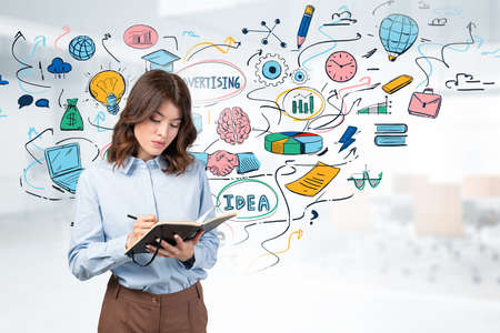 Serious young woman writing in notebook near gray wall with colorful online business sketch. Concept of e commerce