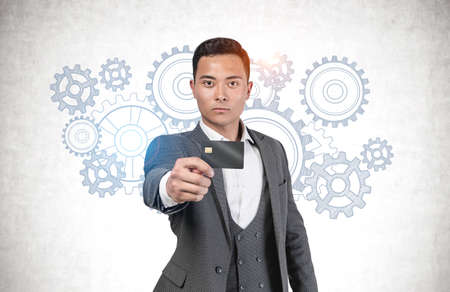 Serious young Asian businessman showing credit card standing near concrete wall with gears sketch drawn on it. Concept of brainstorming and teamwork 版權商用圖片