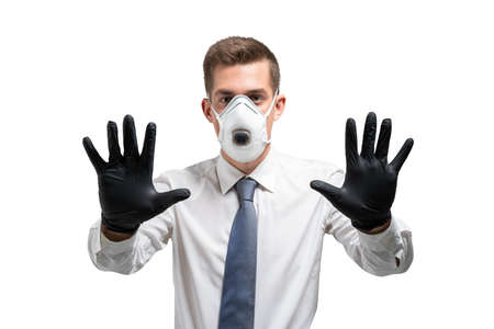 Serious young businessman in gloves and protective mask showing stop sign. Isolated portrait. Covid 19 protection