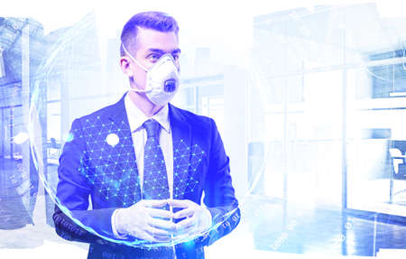 Portrait of serious young European businessman in elegant suit, protective mask and rubber gloves standing in blurry office with double exposure of planet hologram. Toned image Reklamní fotografie