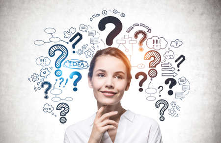 Smiling young European businesswoman standing near concrete wall with question marks and business icons drawn on it