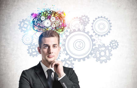 Portrait of pensive young businessman standing near concrete wall with colorful brain sketch drawn on it