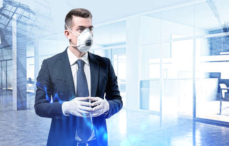Portrait of serious young European businessman in elegant suit, protective mask and rubber gloves standing in blurry office. Toned image double exposure