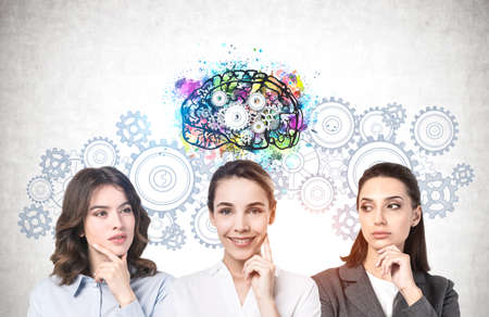 Portrait of three young women standing near concrete wall with brain sketch drawn on it. Concept of education and brainstorming Standard-Bild
