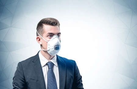 Portrait of serious young European businessman in elegant suit, protective mask and rubber gloves standing near gray wall. Mock up