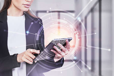 Unrecognizable young businesswoman using tablet in blurry office with double exposure of network interface. Toned image