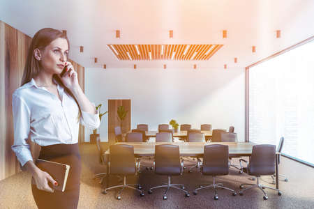 Blonde young businesswoman talking on smartphone in meeting room with white and wooden walls and two conference tables. Toned image 免版税图像 - 153371538