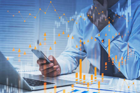 Thoughtful young businessman with smartphone and laptop working in blurry office with double exposure of financial charts. Toned image