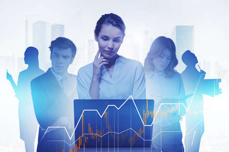 Businesswoman with laptop and her team working together in blurry abstract city with double exposure of financial graph. Toned image