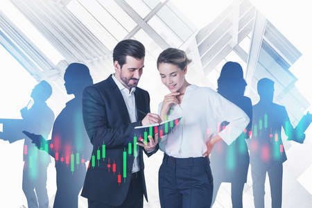 Smiling young businessman and businesswoman standing with notebook and their team in blurry abstract city with double exposure of financial charts. Toned image 免版税图像 - 153371557