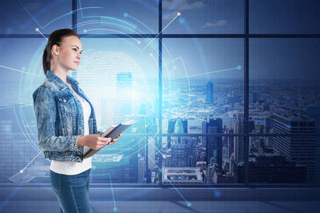 Side view of young businesswoman with notebook standing in panoramic office with double exposure of network interface. Toned image