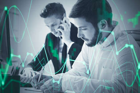 Portrait of two young businessmen working together in blurry office with double exposure of financial chart. Toned image 免版税图像
