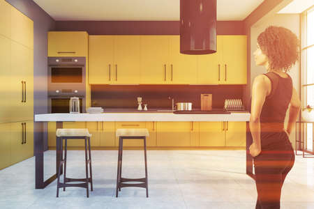 Beautiful young African American woman standing in modern kitchen with gray walls, yellow cupboards and bar with stools. Toned image 免版税图像 - 153315663