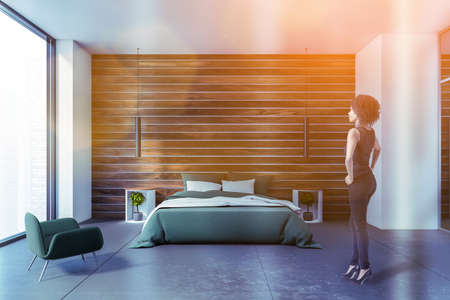Beautiful young African American woman standing in modern bedroom with white and wooden walls and comfortable king size bed. Toned image