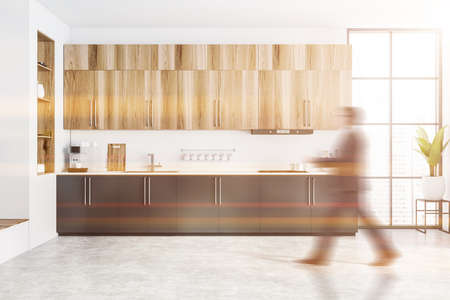 Blurry young man walking in stylish kitchen with white and wooden walls and wooden cabinets. Toned image 免版税图像