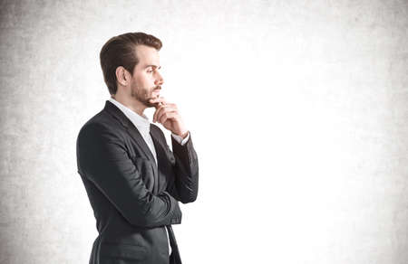 Side portrait of thoughtful young businessman with beard wearing elegant suit near concrete wall. Concept of decision making. Mock up 免版税图像