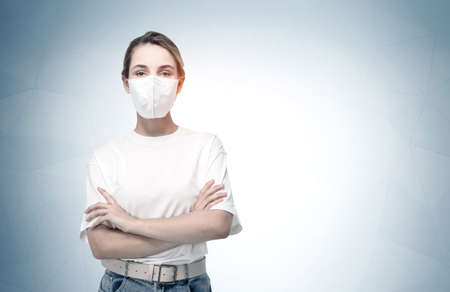 Portrait of young European businesswoman in casual clothes and protective mask standing near gray wall. Mock up
