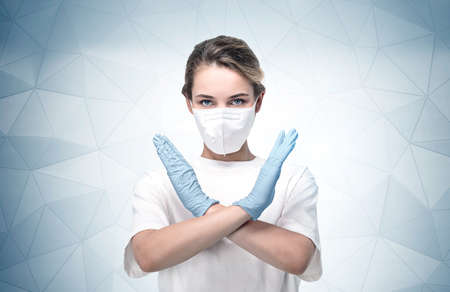 Portrait of serious young European woman in protective mask and glasses showing stop coronavirus sign near gray wall. 免版税图像