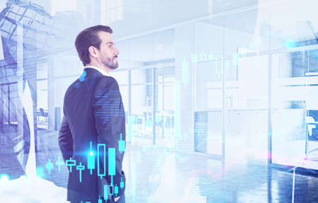 Side view of confident young businessman working in blurry modern office with double exposure of financial charts. Toned image 免版税图像 - 153315713