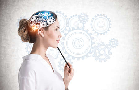 Side view of thoughtful young businesswoman with pencil standing near concrete wall with brain sketch