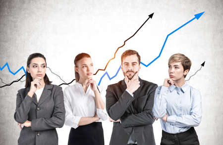 Businessman and three businesswomen standing near concrete wall with growing graphs. Concept of investment and financial success