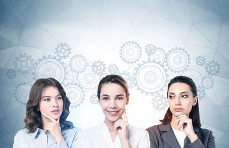 Portrait of three young women thinking and brainstorming together near gray wall with gears drawn on it. Concept of decision making