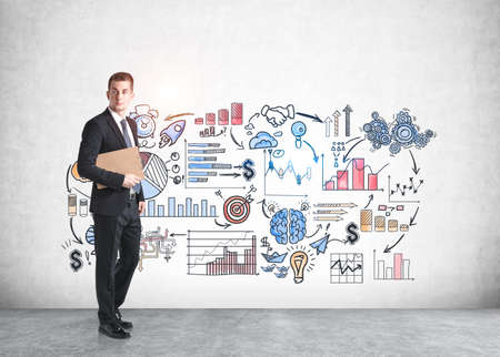 Young European businessman standing with clipboard near concrete wall with business sketch drawn on it. 免版税图像 - 153315730