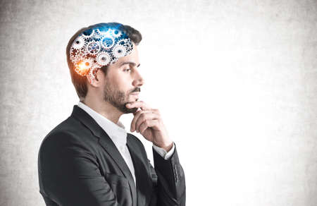 Side view of pensive young bearded man in suit with brain with gears inside his head. Concept of brainstorming. Mock up