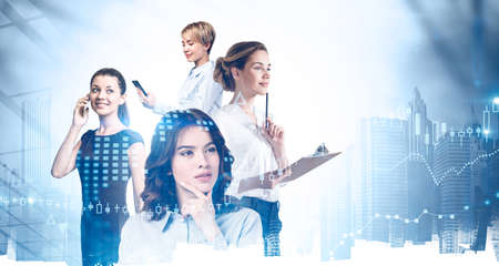 Portrait of four beautiful young businesswomen working together in blurry abstract city with double exposure of planet hologram. Concept of teamwork. Toned image 免版税图像